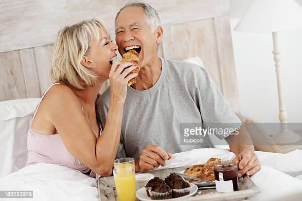 Ältere Frau Füttern älteren Mannes, während ein Frühstück im Bett