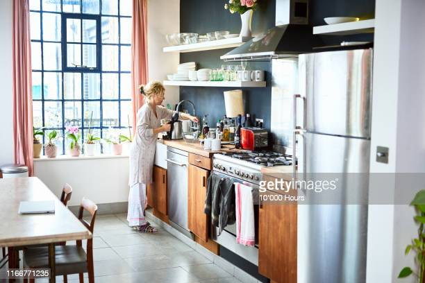 mature woman filling kettle at kitchen sink - making stock pictures, royalty-free photos & images