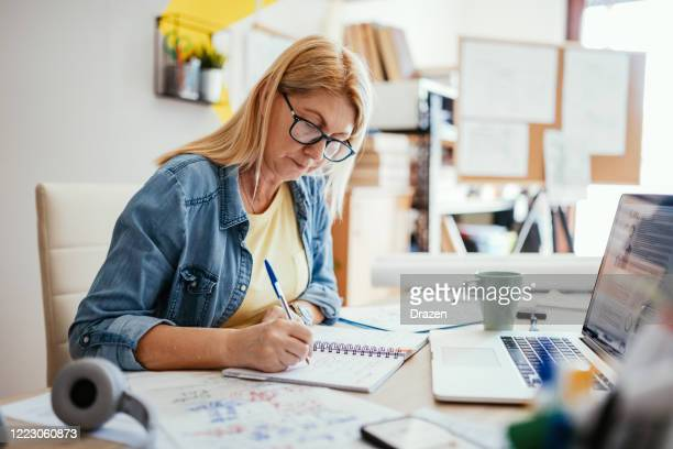 mature woman filling tax documents online - administrator stock pictures, royalty-free photos & images