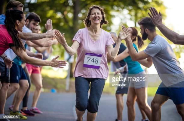 Reife Frau Marathon Zieleinlauf und Begrüßung mit Gruppe von Anhängern.