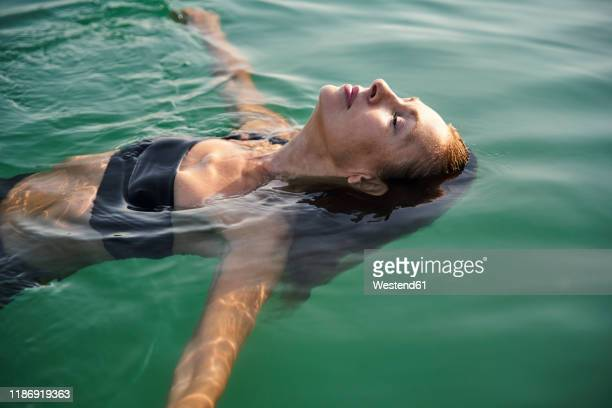 mature woman floating in a lake with closed eyes - relaxation stock-fotos und bilder