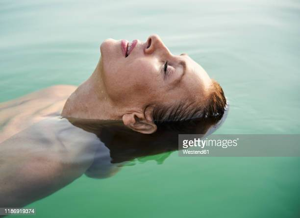 mature woman floating in a lake with closed eyes - alles hinter sich lassen stock-fotos und bilder