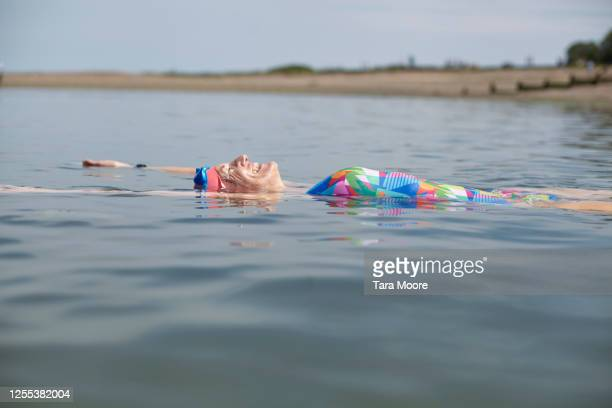 mature woman floating in sea - horizon over water stock pictures, royalty-free photos & images
