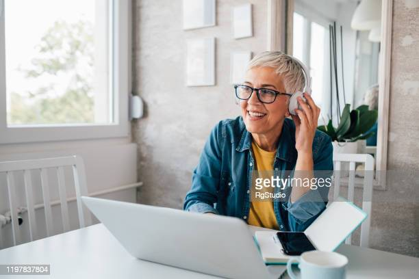 mature woman freelancing from her home office - listening stock pictures, royalty-free photos & images