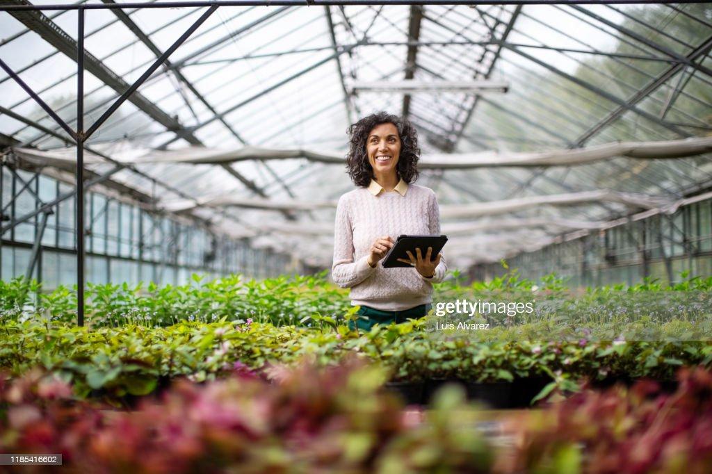 Mature woman gardener with digital tablet at garden center : ストックフォト
