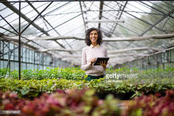 mature woman gardener with digital tablet at garden center - environmental issues stock pictures, royalty-free photos & images