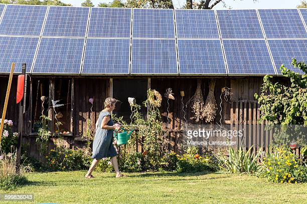 mature woman gardening, walking with watering can - solar equipment stock pictures, royalty-free photos & images