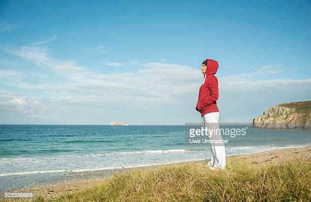 Mature woman gazing at sea view, Camaret-sur-mer, Brittany, France
