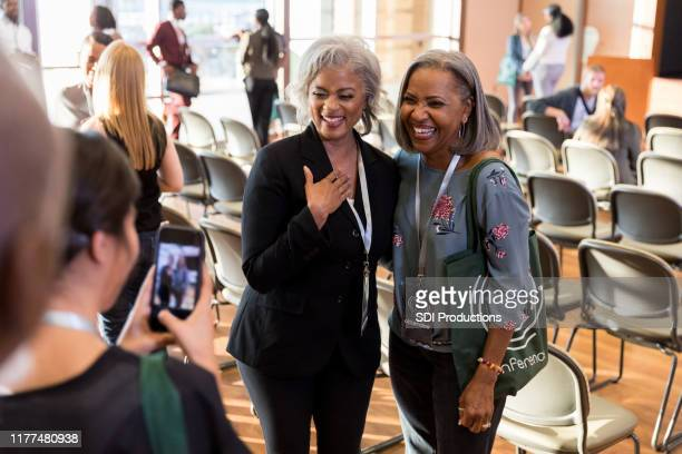 mature woman gets photo taken with expo speaker - attending stock pictures, royalty-free photos & images
