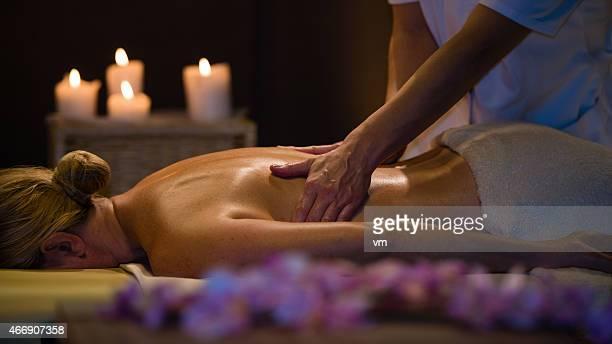 ältere frau erhalten eine massage in einer wunderschönen atmosphäre - erotische massage stock-fotos und bilder