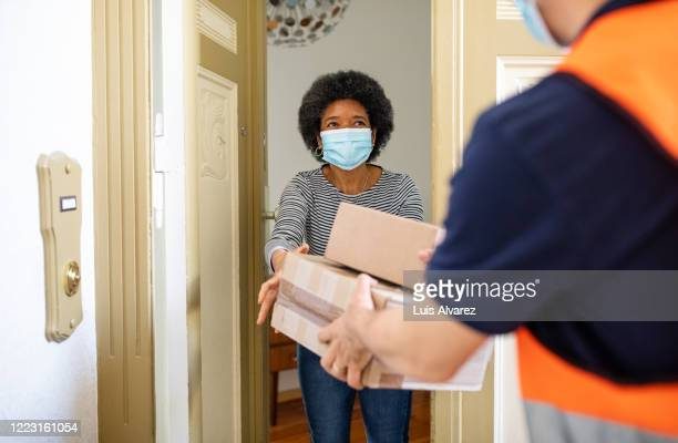 mature woman getting package from delivery person during pandemic - receiving stock pictures, royalty-free photos & images