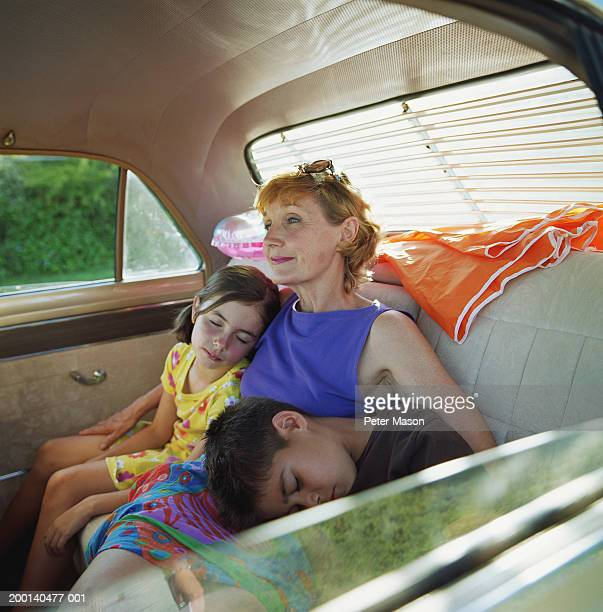 Mature woman, girl and boy (6-8) in back of car, children sleeping