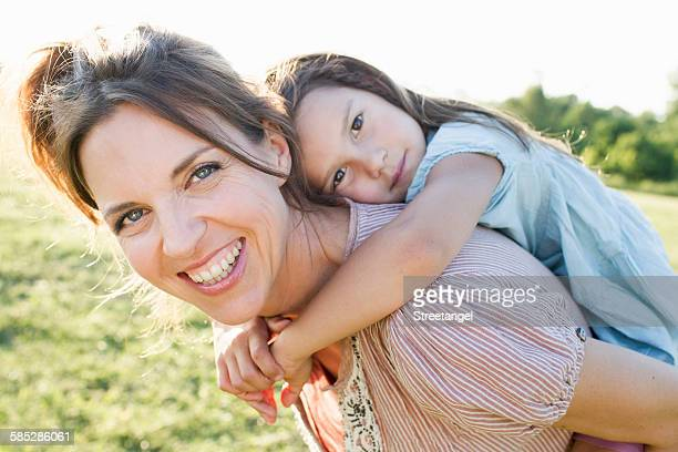 Mature woman giving daughter piggy back ride in park