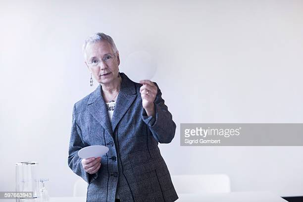 mature woman giving lecture holding up white circle looking at camera - sigrid gombert stock pictures, royalty-free photos & images
