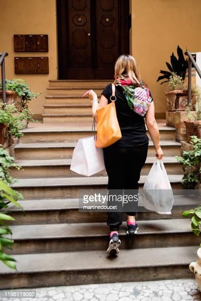 """mujer madura que va a casa después de ir de compras al aire libre en la ciudad. - """"martine doucet"""" or martinedoucet fotografías e imágenes de stock"""