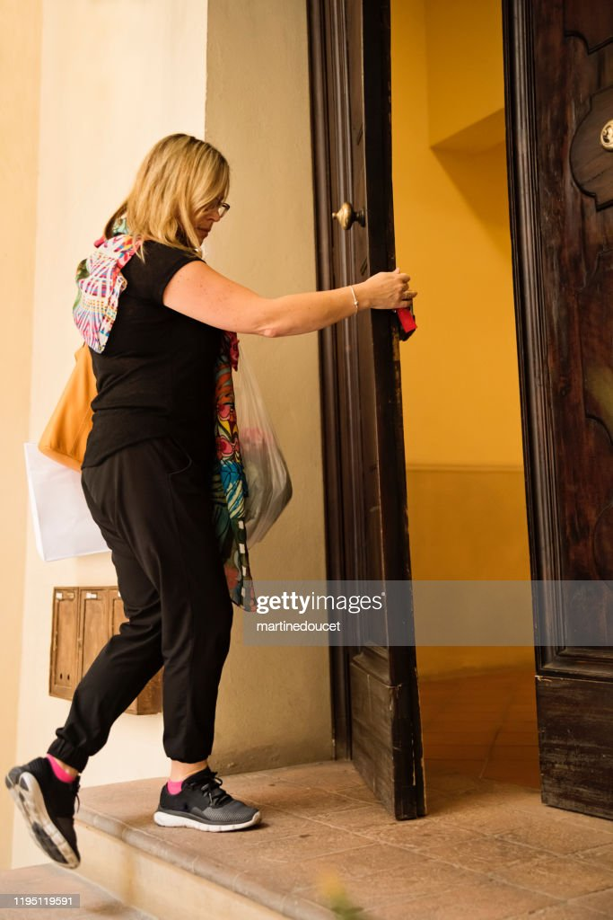 Mature woman going home after shopping outdoors in city. : Stock Photo
