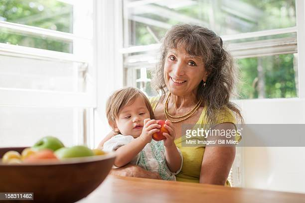 a mature woman, grandparent cradling a 1 year old child, her granddaughter. - 63 year old female stock pictures, royalty-free photos & images
