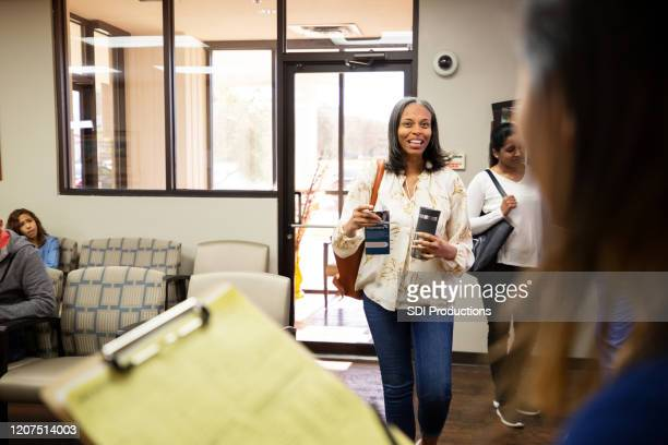 mature woman greets a waiting nurse in a medical clinic - pamphlet stock pictures, royalty-free photos & images