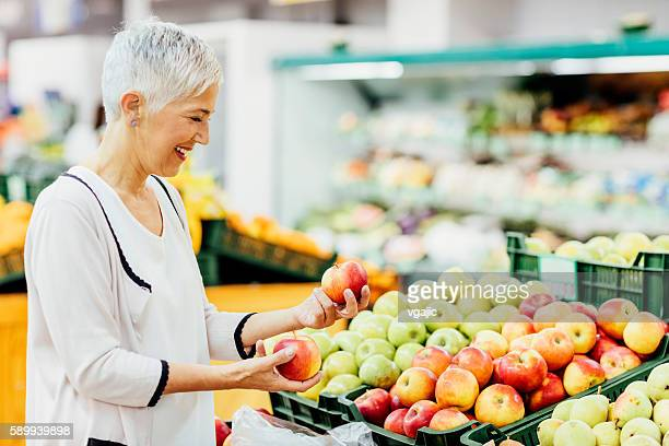 mature woman groceries shopping. - apple fruit stock photos and pictures
