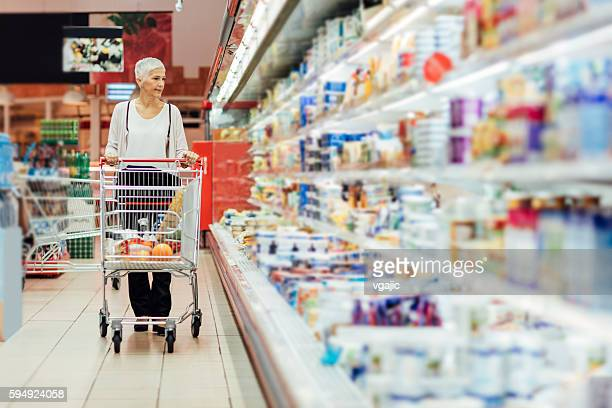 mature woman groceries shopping. - shopping cart stock pictures, royalty-free photos & images