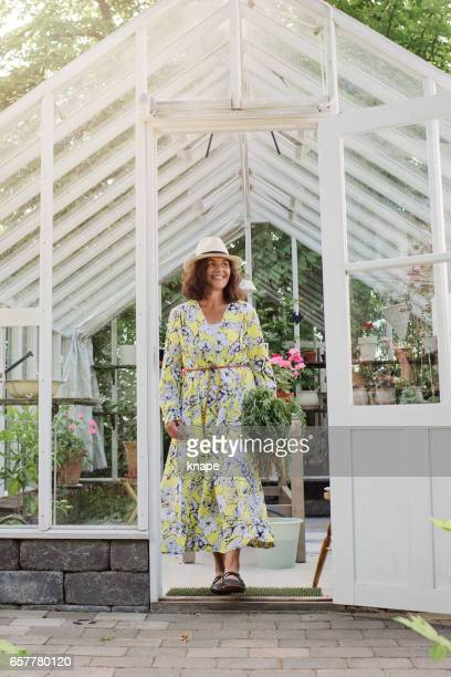 Mature woman growing homegrown food outside her greenhouse