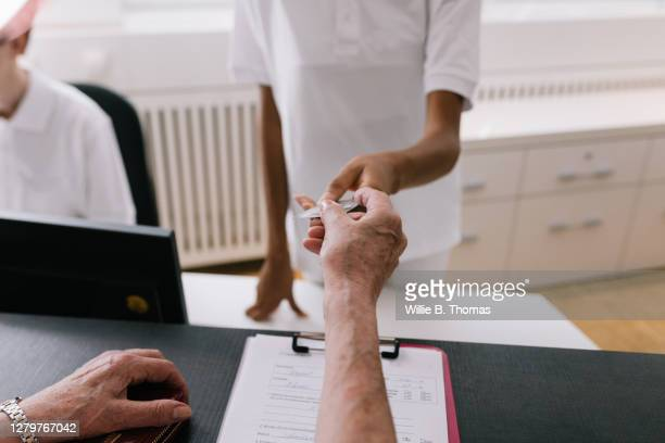 mature woman handing medical insurance card to clinic receptionist - medical receptionist uniforms stock pictures, royalty-free photos & images