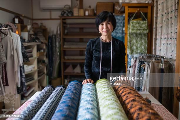 熟女彼女は製造後に設計された繊維を終えた生地に満足して - ワーキングシニア ストックフォトと画像