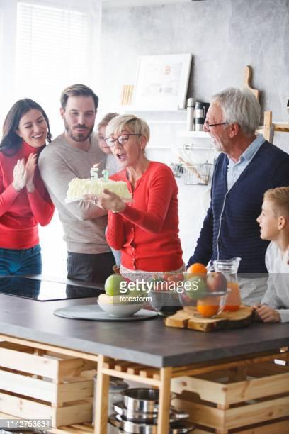 femme d'âge mûr ayant une fête d'anniversaire à la maison - groupe moyen de personnes photos et images de collection