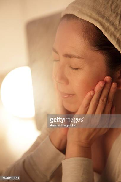 mature woman having beauty treatment with facial steamer, at night - 人体部位 ストックフォトと画像