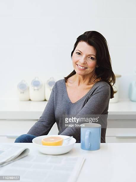 mature woman having breakfast - femme 50 ans brune photos et images de collection