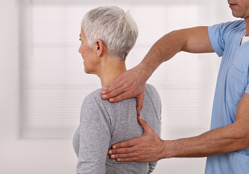 Mature Woman having chiropractic back adjustment. Osteopathy, Physiotherapy, Sport injury rehabilitation concept, holistic care 1132352012