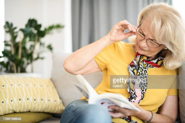 mature woman having eyesight problems reading a book. - problems stock pictures, royalty-free photos & images