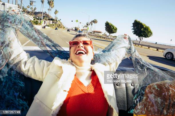 mature woman having fun in the back of a convertible - one mature woman only stock pictures, royalty-free photos & images