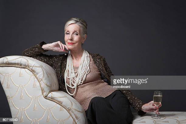 mature woman having glass of champagne - formal portrait fotografías e imágenes de stock