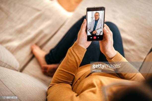 mature woman having online consultation with doctor at home on smartphone - telemedicine stock pictures, royalty-free photos & images