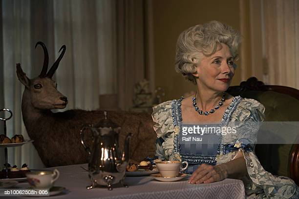 Mature woman having tea, smiling
