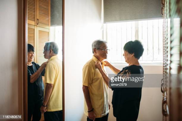 mature woman helping her husband to getting dressed - adjusting necktie stock pictures, royalty-free photos & images