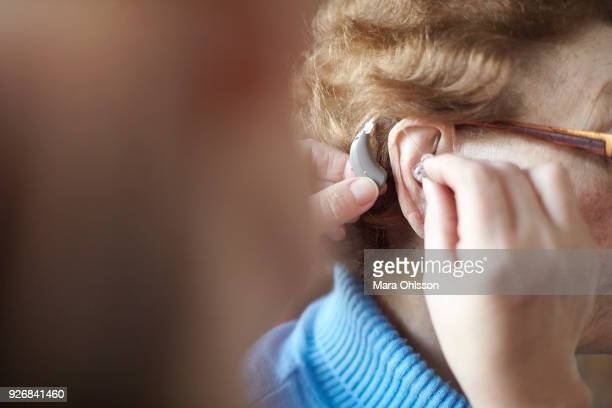 Mature woman helping senior woman insert hearing aid, close-up, differential focus