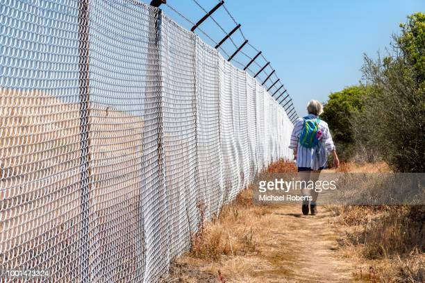 Mature woman hiker and security fencing on the Pembrokeshire coast path near Milford Haven