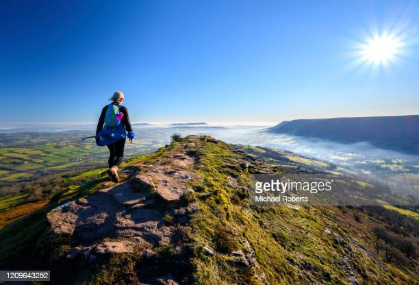 mature woman hiker on black hill (the cat's back) in the black mountains, brecon beacons national park - vacations stock pictures, royalty-free photos & images