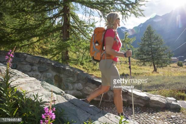 donna matura escursioni lungo sentiero di ciottoli - monte cervino foto e immagini stock