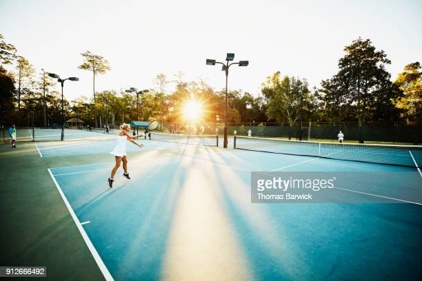 Mature woman hitting forehand during early morning tennis match