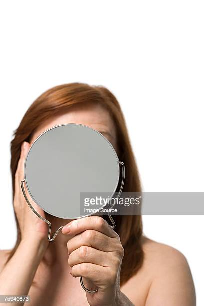 mature woman holding a hand mirror - hand mirror stock pictures, royalty-free photos & images