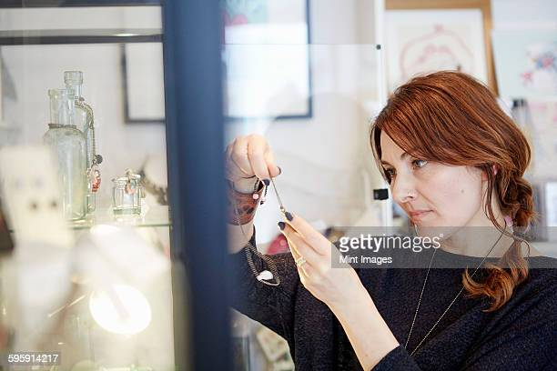 A mature woman holding a piece of jewellery or a small object, a customer or manager in a gift and craft shop.