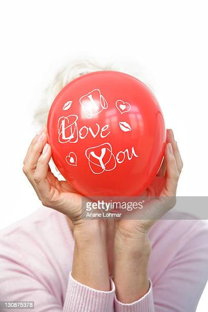 A mature woman holding a red balloon saying I love you, in front of her face