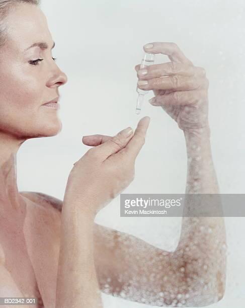 Mature woman holding ampoule, squeezing liquid onto finger