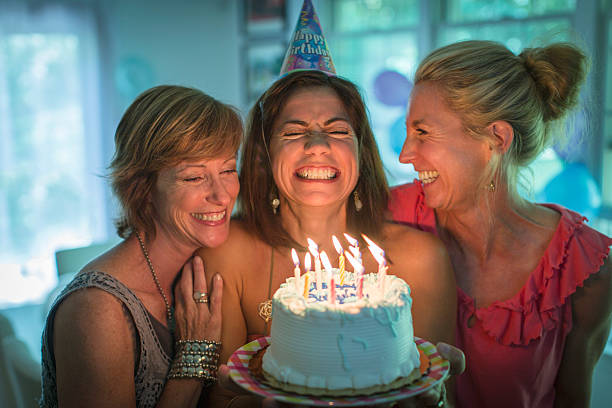 mature woman holding birthday cake, making wish while two friends look on - best friend birthday cake stock pictures, royalty-free photos & images
