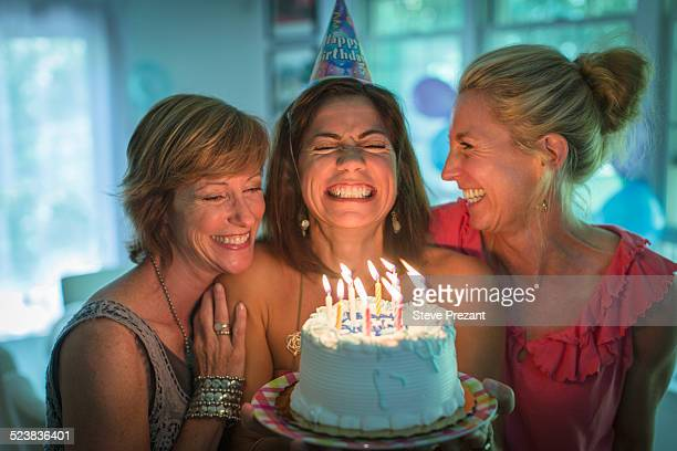 mature woman holding birthday cake, making wish while two friends look on - birthday cake stock pictures, royalty-free photos & images