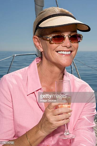 mature woman holding champagne flute - alleen één oudere vrouw stockfoto's en -beelden