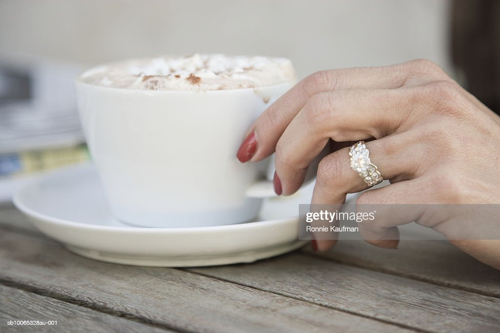 Mature woman holding cup of cappuccino, close-up : Foto stock